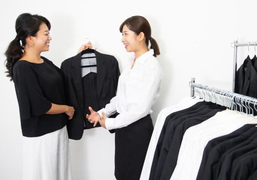 女性のヘアメイクが女子就活生にレンタルスーツを選ぶ写真