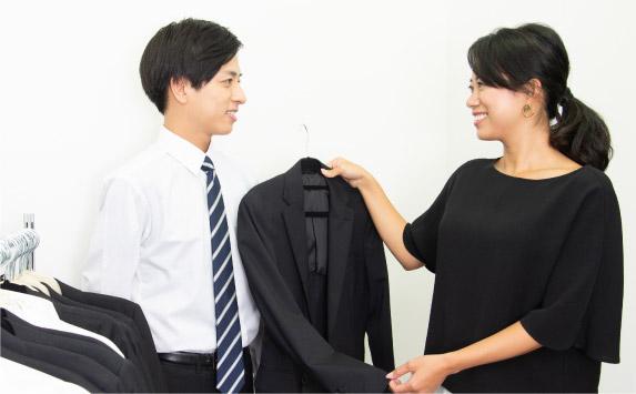 女性のヘアメイクが男子就活生にレンタルスーツを選ぶ写真