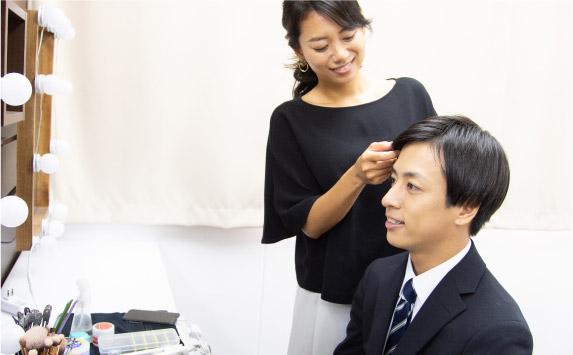 女性のヘアメイクが男子就活生にヘアメイクを施術する写真