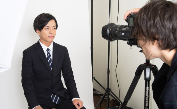 プロカメラマンが男子就活生を撮影する写真