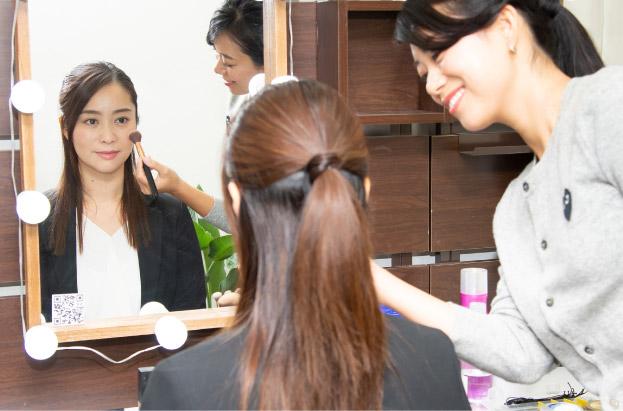 女性のヘアメイクが女子就活生にヘアメイクを施術する写真