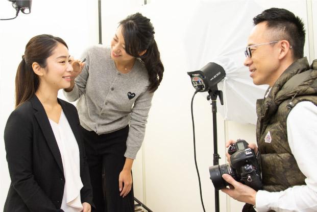女性のヘアメイクとカメラマンが女子就活生を撮影する写真